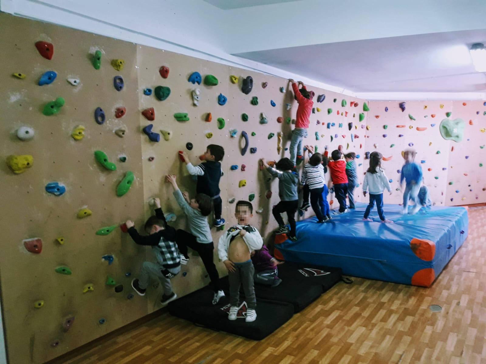 Niños disfrutando de la escalada en su colegio
